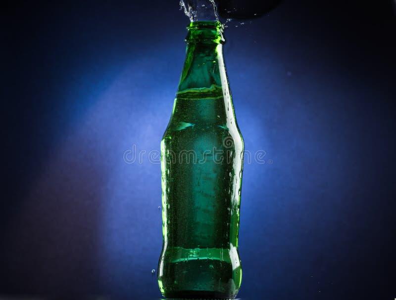 Падая и скача зеленая бутылка с разливать жидкость на голубой предпосылке градиента стоковое фото