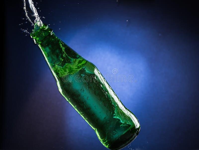 Падая и скача зеленая бутылка с разливать жидкость на голубой предпосылке градиента стоковые фото