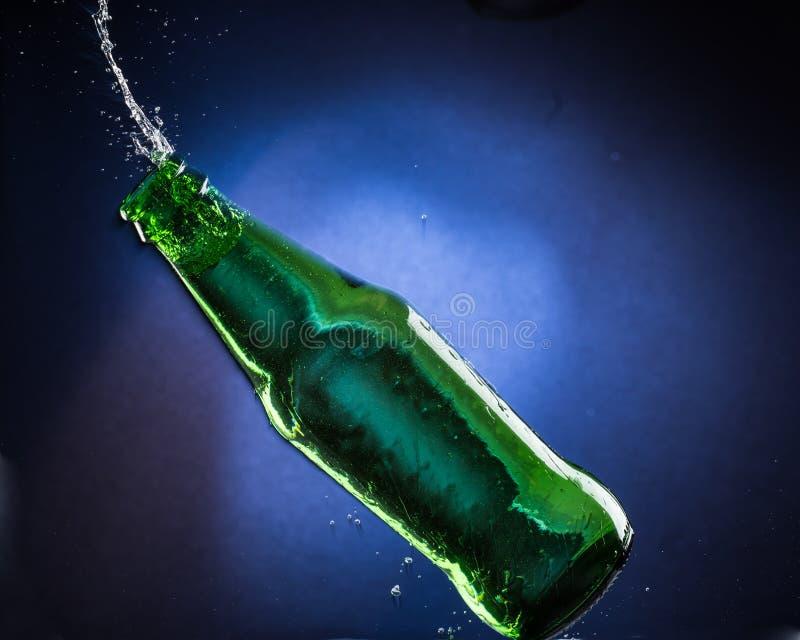 Падая и скача зеленая бутылка с разливать жидкость на голубой предпосылке градиента стоковое фото rf