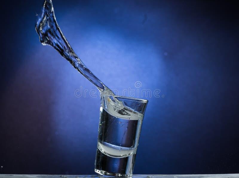 Падая и скача стекло с разливать жидкость на голубой предпосылке градиента стоковые изображения