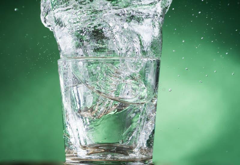 Падая небольшие стекла и разливать воду на зеленой предпосылке стоковое фото