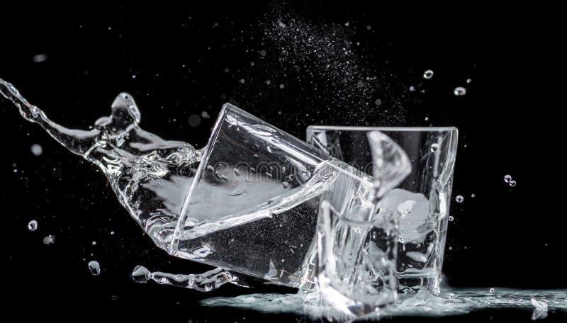 Падая небольшие стекла и разливать воду на черной предпосылке стоковая фотография