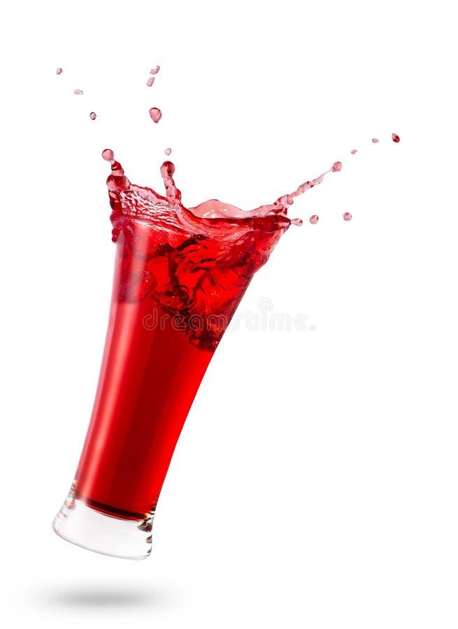 Падая стекло с красным соком стоковое фото