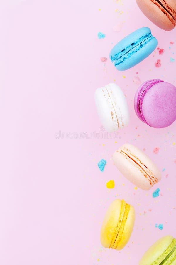 Падая macaron или macaroon торта на розовой пастельной предпосылке Красочные печенья миндалины на десерте стоковые изображения rf