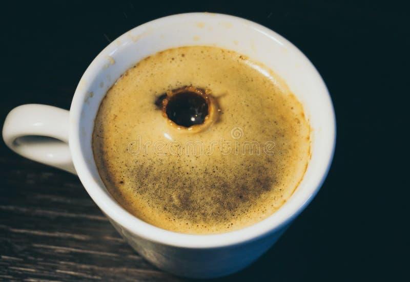 Падение молока понижаясь в чашку кофе стоковое изображение rf