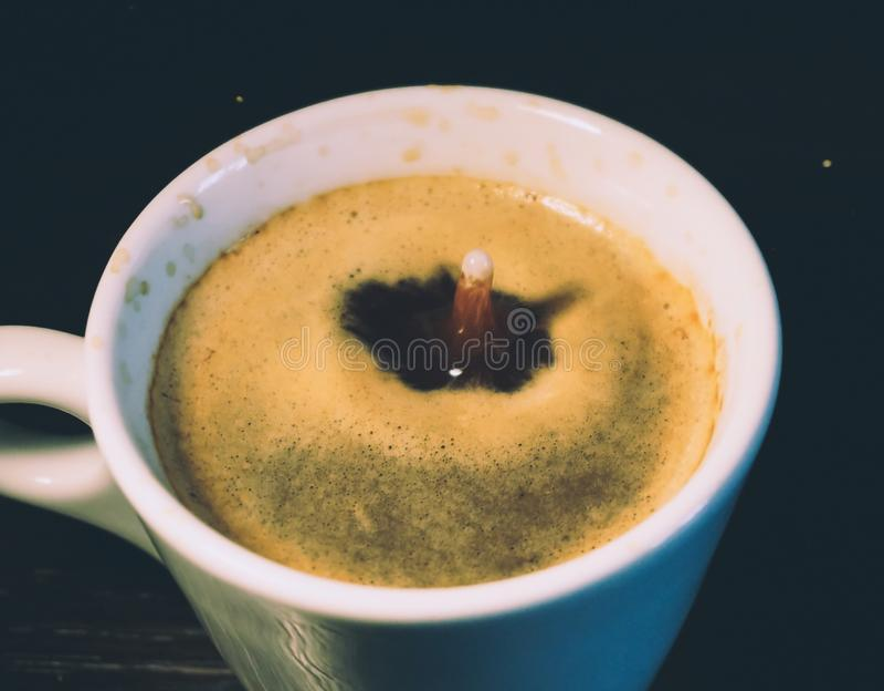Падение молока понижаясь в чашку кофе стоковые изображения rf