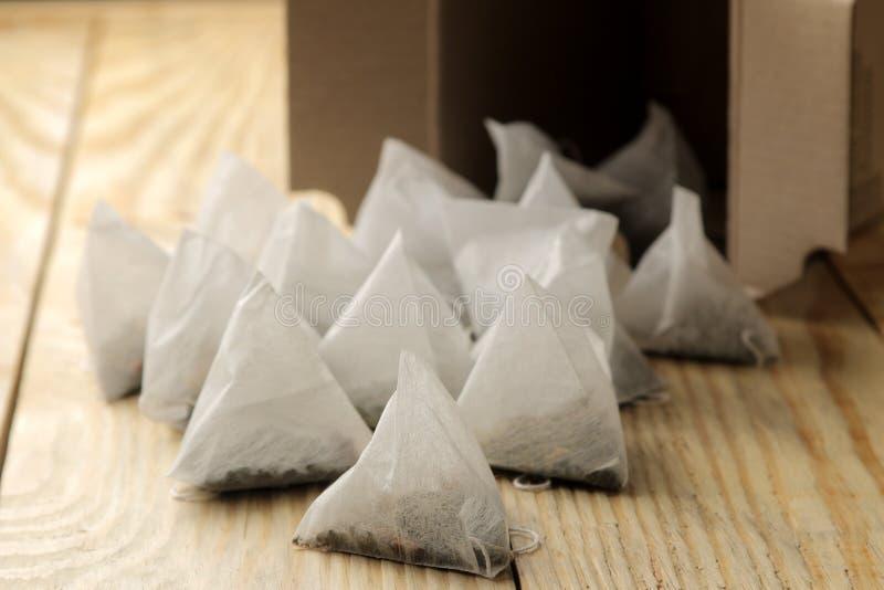 Падение пирамиды пакетиков чая из конца-вверх коробки на естественном деревянном столе стоковое фото rf