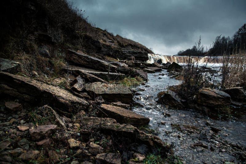 Падения вдоль заводи и камней с драматическим небом стоковое фото rf
