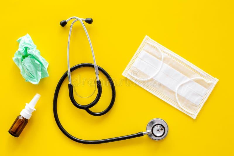 Падения гриппа Идущая концепция носа Сморщенная салфетка около стетоскопа и лицевой щиток гермошлема на желтом взгляд сверху пред стоковое фото