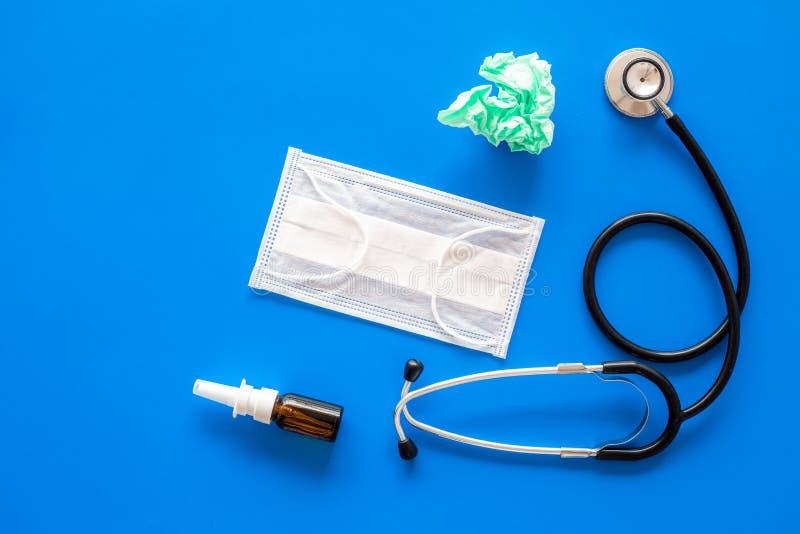 Падения гриппа Идущая концепция носа Сморщенная салфетка около стетоскопа и лицевой щиток гермошлема на голубом космосе экземпляр стоковые фото