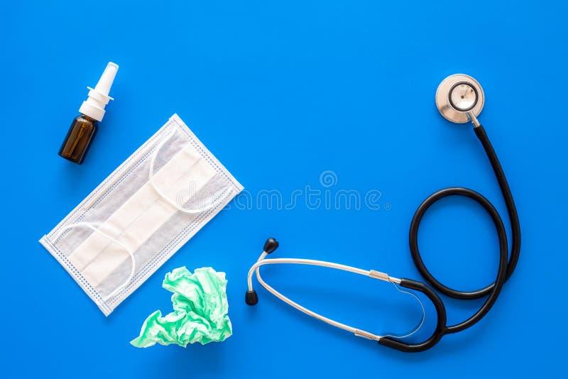 Падения гриппа Идущая концепция носа Сморщенная салфетка около стетоскопа и лицевой щиток гермошлема на голубом космосе экземпляр стоковое фото rf