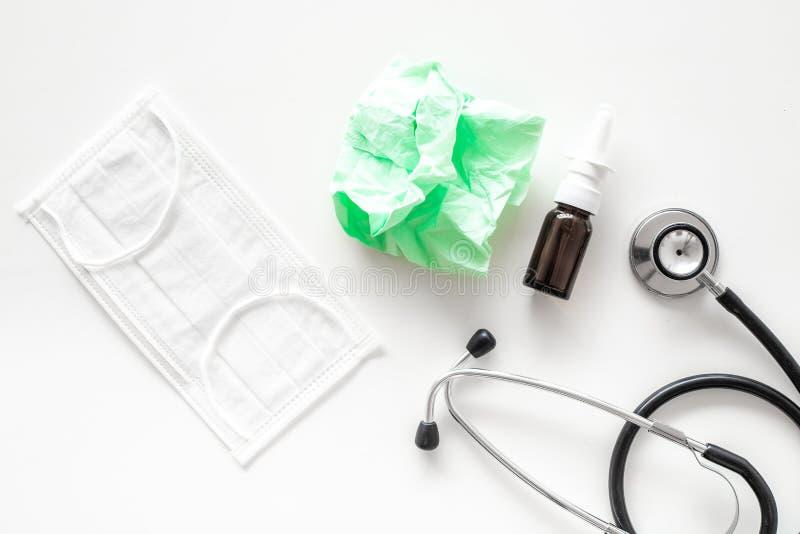 Падения гриппа Идущая концепция носа Сморщенная салфетка около стетоскопа и лицевой щиток гермошлема на белом взгляд сверху предп стоковое изображение