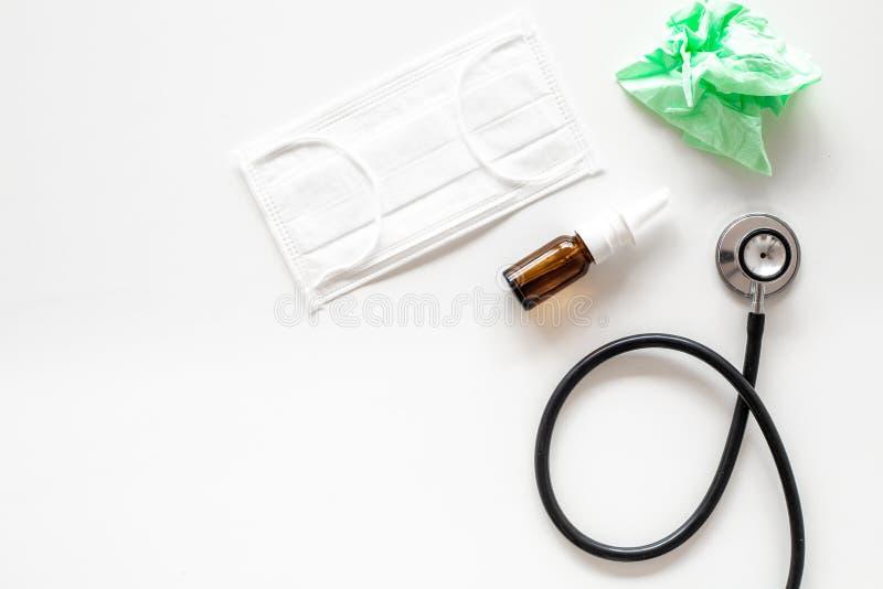 Падения гриппа Идущая концепция носа Сморщенная салфетка около стетоскопа и лицевой щиток гермошлема на белом взгляд сверху предп стоковая фотография rf