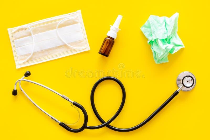 Падения гриппа Идущая концепция носа Сморщенная салфетка около стетоскопа и лицевой щиток гермошлема на желтом взгляд сверху пред стоковое изображение