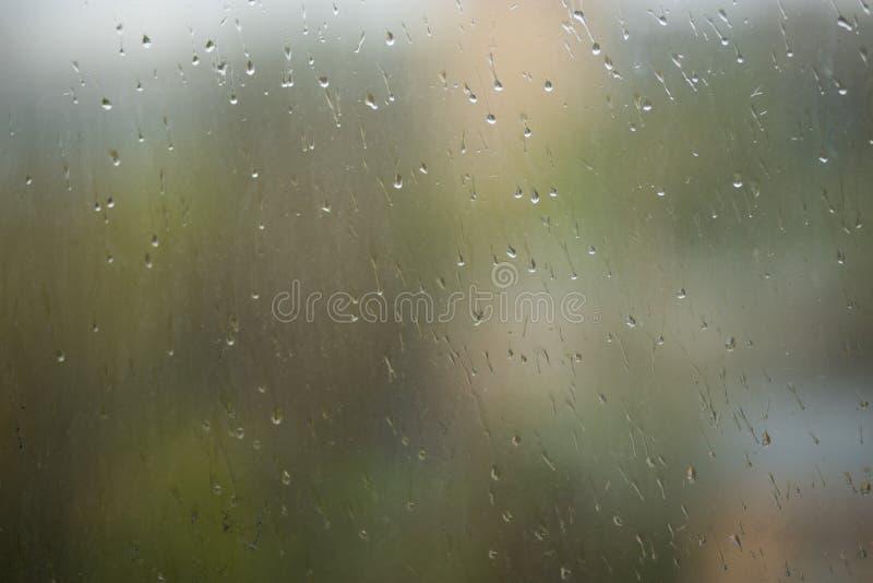 Падения дождя бежать вниз с грязной стеклянной специализированной части окна стоковая фотография rf