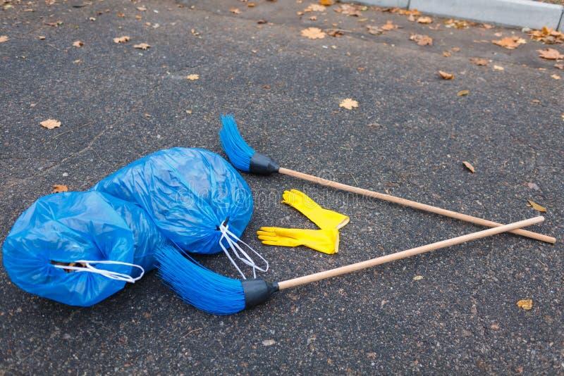 2 пакета отброса и 2 веников лежат на дороге в парке стоковые фотографии rf