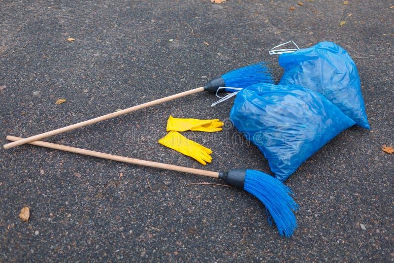 2 пакета отброса и 2 веников лежат рядом с ложью на дороге в парке стоковые фото