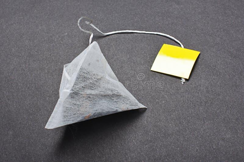 Пакетик чая формы пирамиды на темной предпосылке стоковое изображение rf
