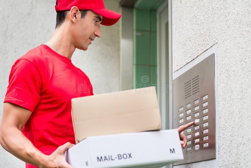 Пакеты нося почты работника доставляющего покупки на дом используя внутренную связь стоковые изображения rf