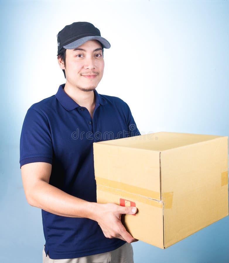 Пакет нося o усмехаясь красивого азиатского работника доставляющего покупки на дом давая и стоковые фото