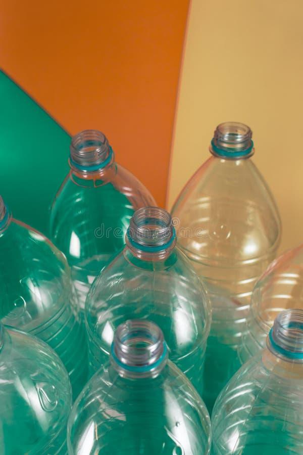 Пакет 8 пустого и recyclable пластиковых бутылок с водой, без крышек, голубое уплотнение, в полиэтиленовом пакете, на покрашенной стоковое изображение