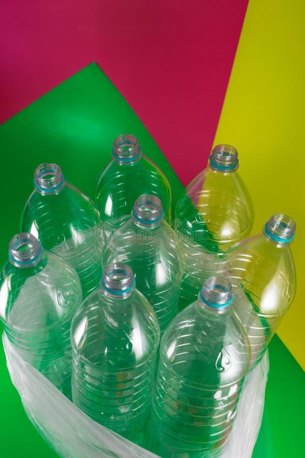 Пакет 8 пустого и recyclable пластиковых бутылок с водой, без крышек, голубое уплотнение, в полиэтиленовом пакете, на геометричес стоковое фото rf