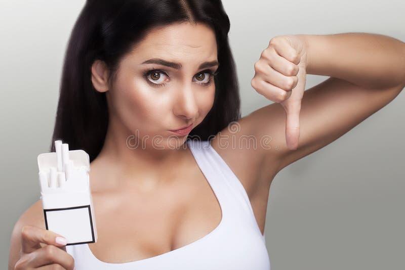 Пакет сигарет в руках женщины Изумленный взгляд на сигаретах стоковое изображение