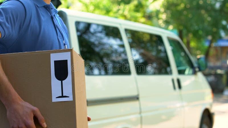 Пакет удерживания работника доставляющего покупки на дом отметил хрупкая, осторожная ориентация для работы, пересылка стоковое изображение rf