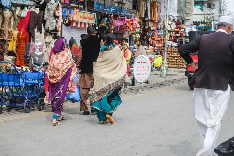 Пакистанские люди в традиционном платье идя на торговую улицу стоковые фото