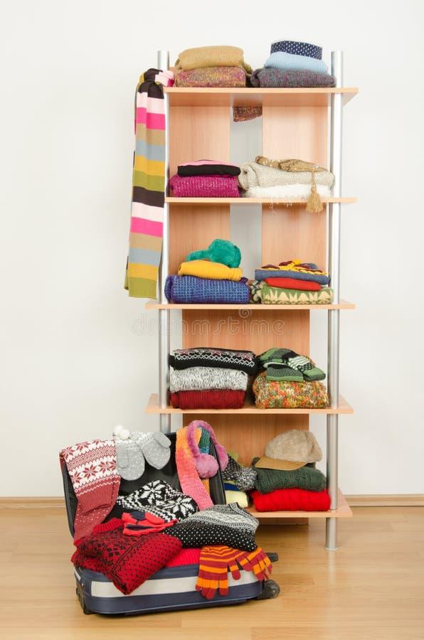 Паковать чемодан на каникулы зимы Шкаф с славно аранжированными одеждами и полным багажом стоковые изображения
