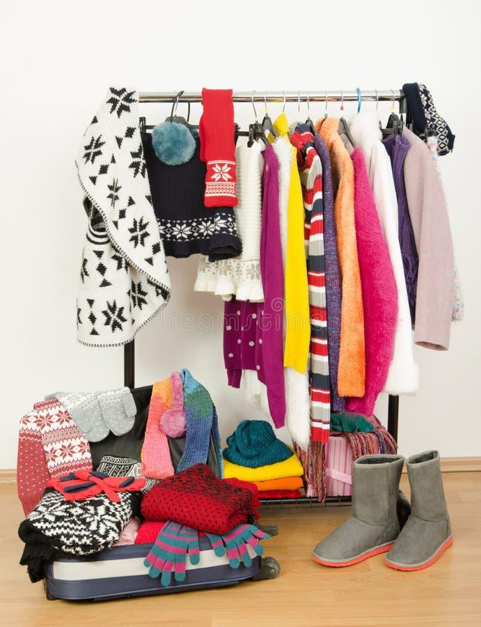 Паковать чемодан на каникулы зимы Шкаф с славно аранжированными одеждами и полным багажом стоковое изображение