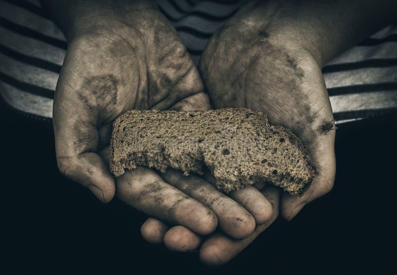 Пакостные руки бездомного бедного человека с куском хлеба Концепция бедности и социального неравенства стоковые изображения rf