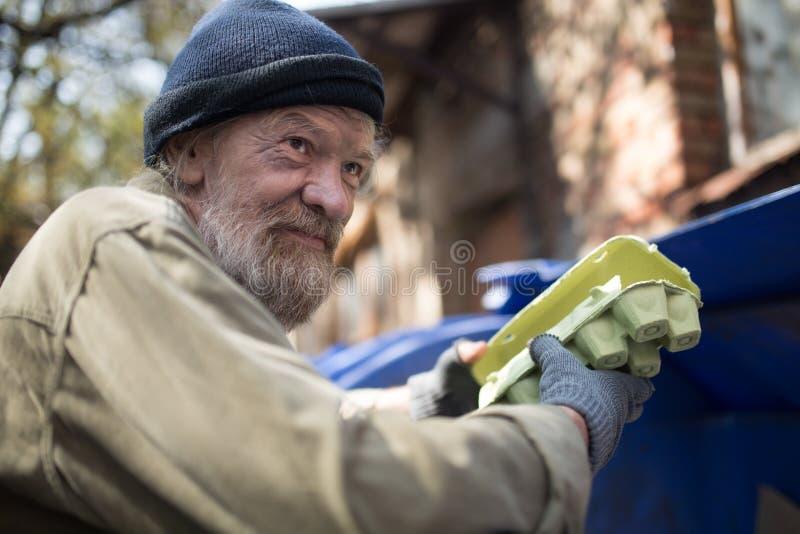Пакостный бездомный человек держа упаковку для яичек, готовя мусорный бак стоковые фотографии rf