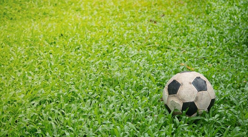 Пакостный используемый футбол на траве Старый футбол на зеленой траве стоковое изображение rf