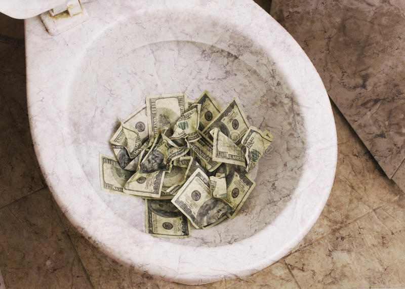 Пакостный туалет с деньгами стоковые фото