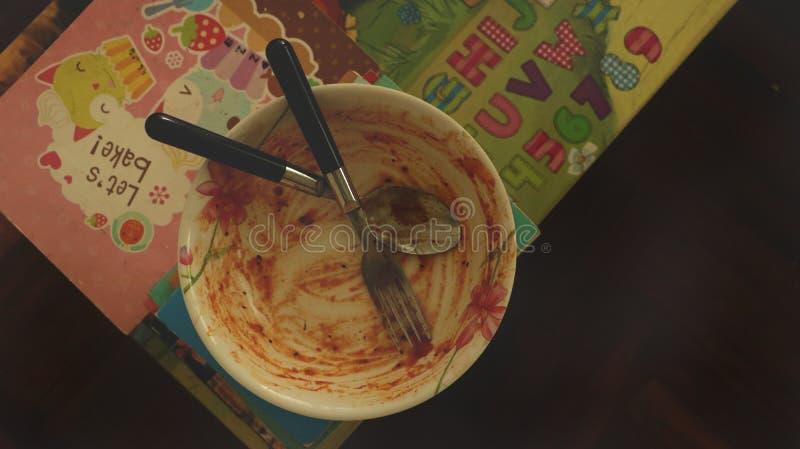 Пакостный шар томатного соуса запятнанный с вилкой и ложкой - красочной таблицей стоковое фото
