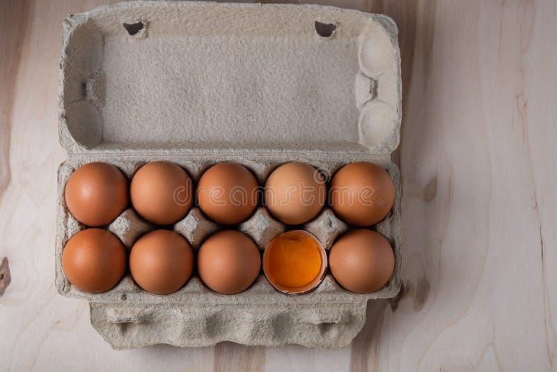 Пакуя яйца цыпленка с одним сломанные на деревянной предпосылке стоковое фото rf