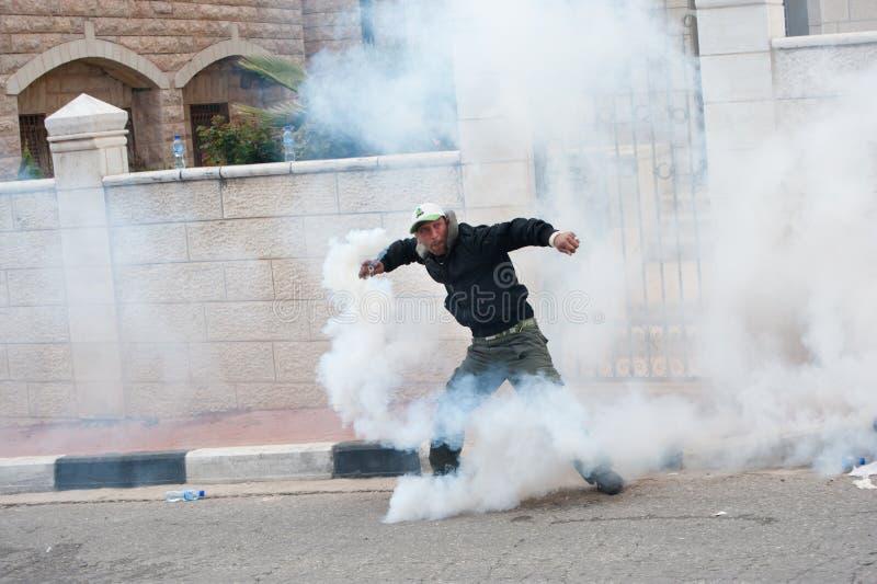 Палестинец бросает назад слезоточивый газ стоковая фотография rf