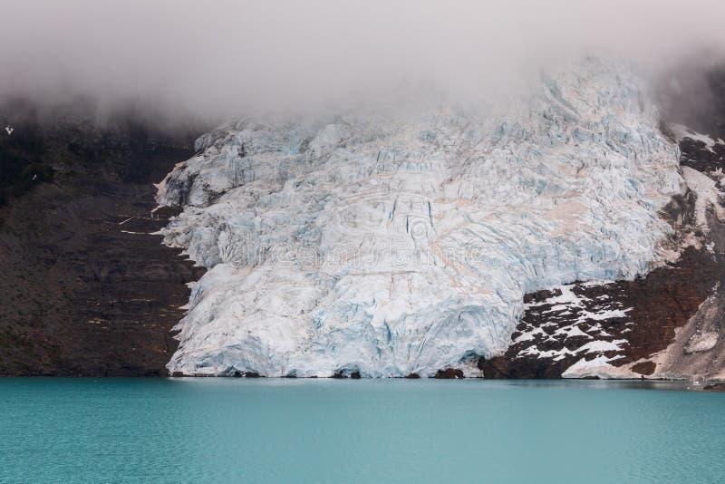 Палец ноги ледника на озере с тяжелым облаком выше стоковая фотография rf