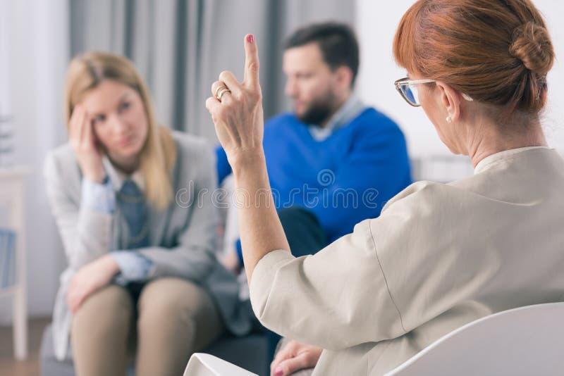 Палец показа одного терапевта пока говорящ с ее пациентами во время терапии стоковое изображение