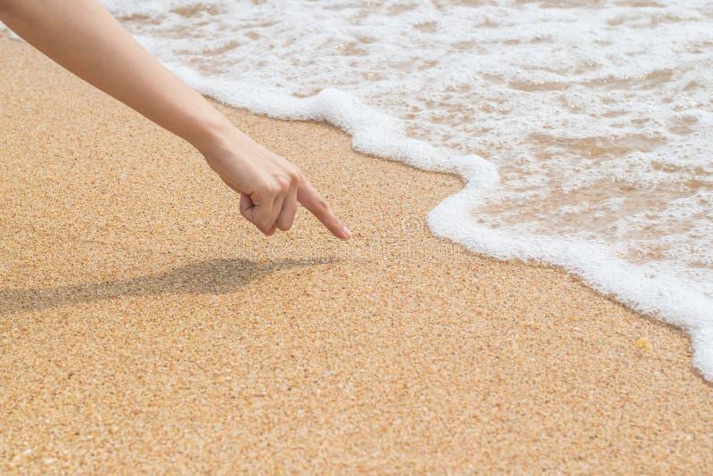 Палец ` s женщины рисует на песке пляжа стоковая фотография rf