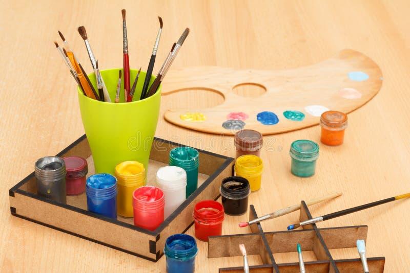 Палитра и коробка с красочными красками и чашкой с paintbrushes стоковые изображения