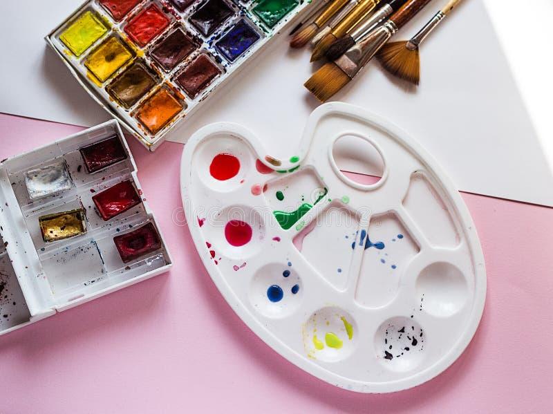 Палитра с набором красок акварели и щеток на розовой предпосылке, инструментов художника стоковое изображение