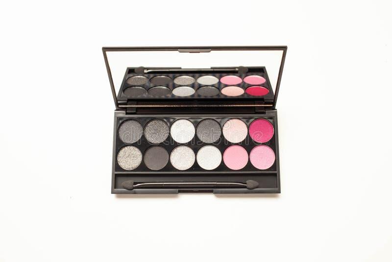 Палитра multicolor косметики составляет с зеркалом, пинком и серой палитрой тени глаза стоковая фотография rf