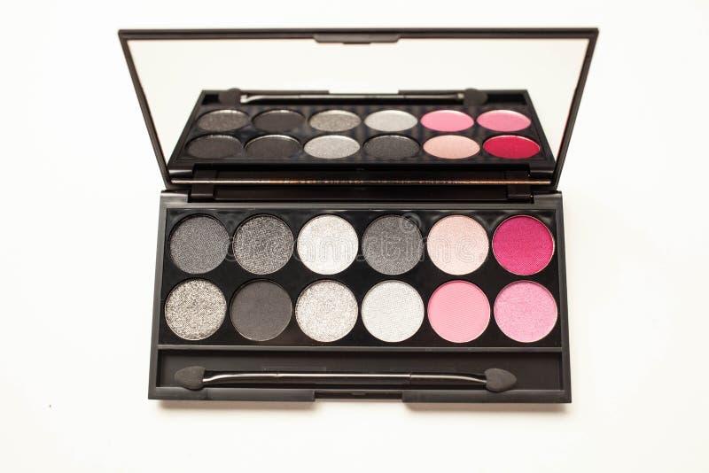Палитра multicolor косметики составляет с зеркалом, пинком и серым концом палитры тени глаза вверх стоковая фотография