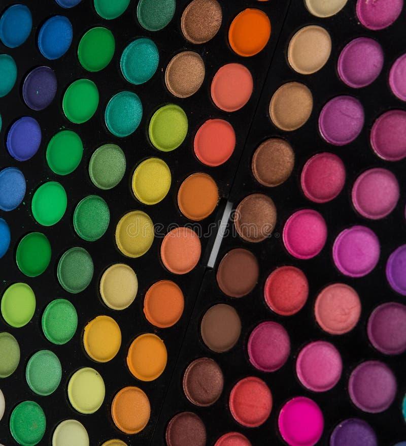 Палитра multicolor косметики составляет, палитра тени глаза, красочная текстура теней, круглые круги цвета, изолированные на бело стоковое фото rf