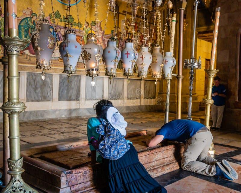 Паломники Unindentifed на камне мазать в церков святого Sepulchre стоковое изображение