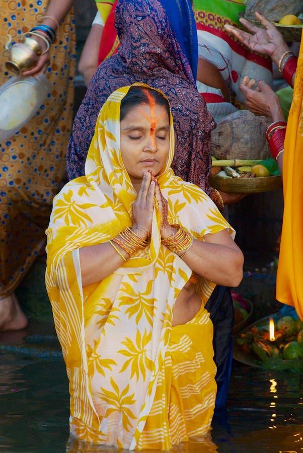 Паломник женщины молит на банке святого Ганга на восходе солнца с другими паломниками на предпосылке в Варанаси, Индии стоковое фото