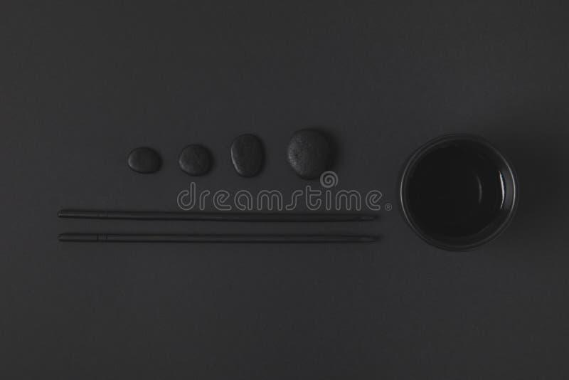 Палочка с китайскими чашкой и камешками чая на черноте стоковая фотография rf