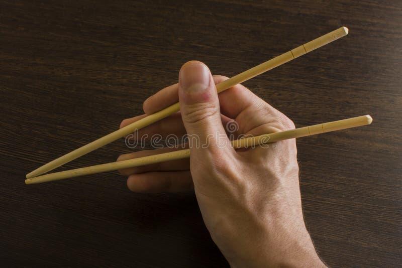 Палочки в правой руке на предпосылке древесины стоковые изображения